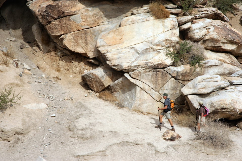 Two hikers on a dirt trail next to a big rock wall at Lake Mead National Recreation Area