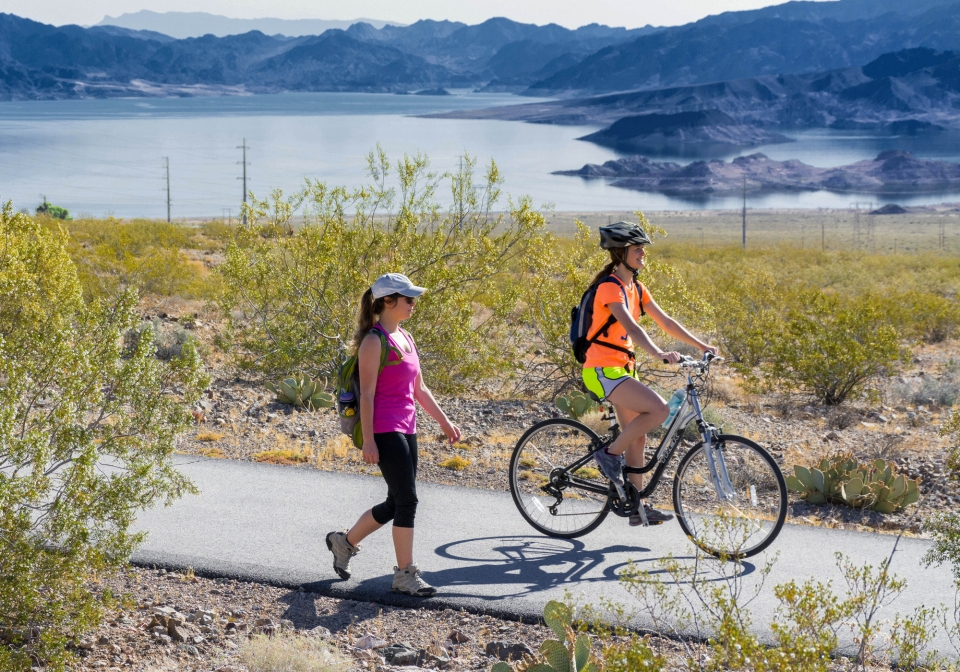 Hiker and cyclist on paved trail, lake and mountains in background