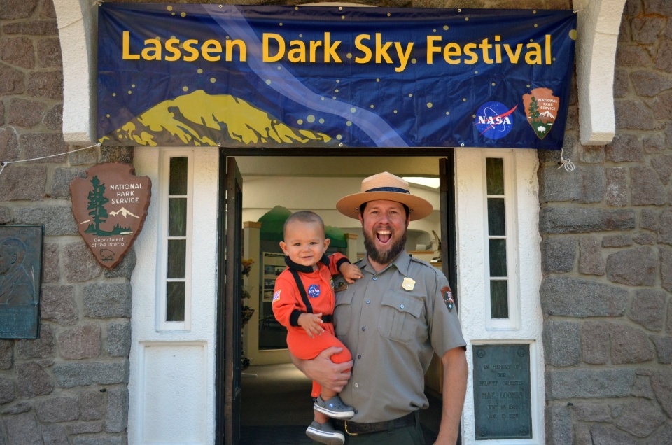 A Dark Sky Festival ranger holding a baby in an astronaut suit at Lassen National Park