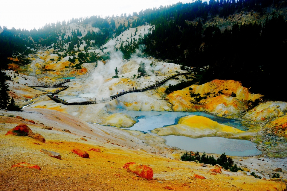 Vibrant yellow and orange hues paint the terrain surrounding the light blue boiling mud pots as steam arises at Bumpass Hell in Lassen Volcanic National Park.