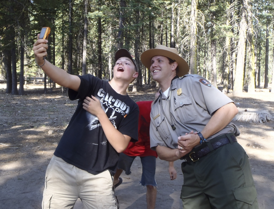 A visitor and ranger take a selfie picture, with trees in the background