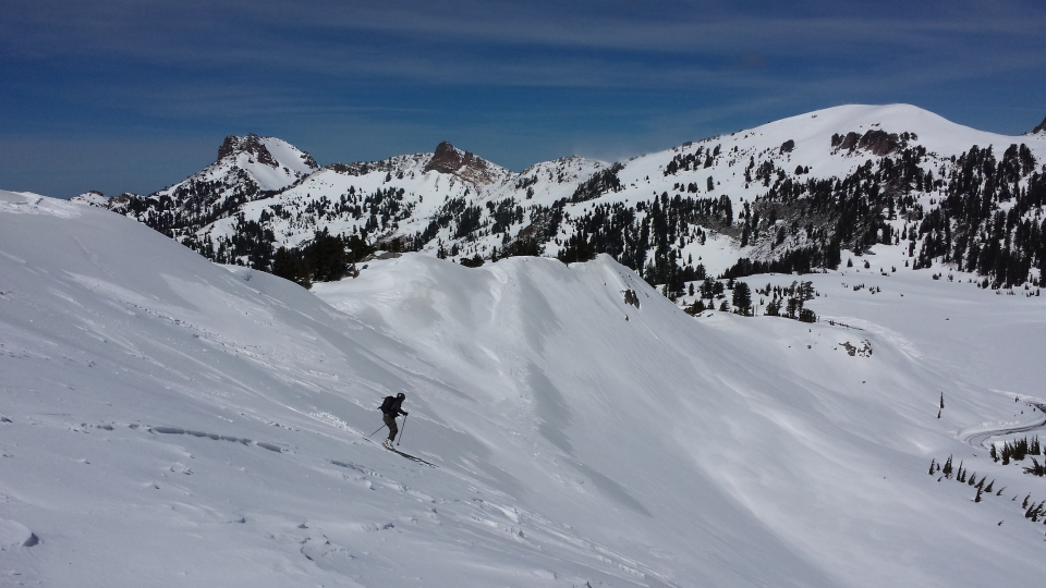 A skiier skiing down a snow-covered slope with the main park road to the right and Mount Diller and Pilot Pinnacle in the background to the left.