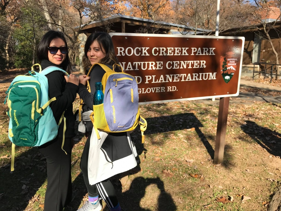 Two women standing next to a Rock Creek Park sign