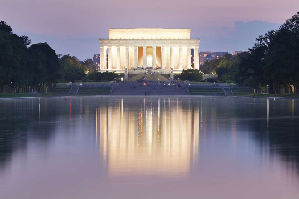 Lincoln Memorial lit up at night against a purple and lavender sky.