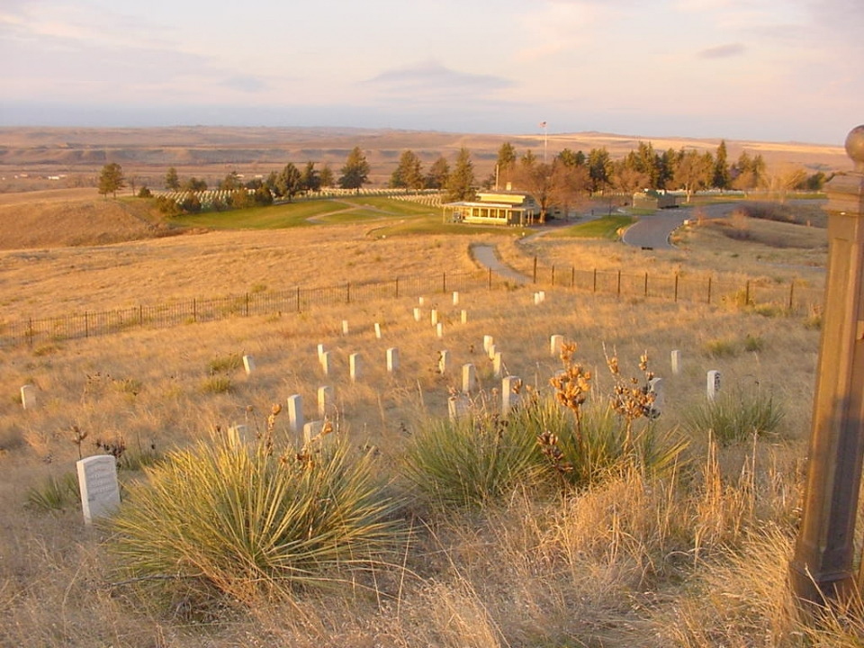 A dry, grassy plain slopes downwards toward the visitor center at Little Bighorn Battlefield National Monument. In the foreground, on Last Stand Hill, small white headstones dot the cemetery.