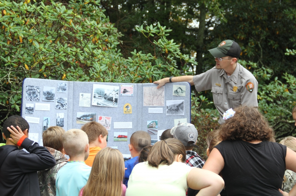 A National Park Service employee showing a display board with the history of railroads
