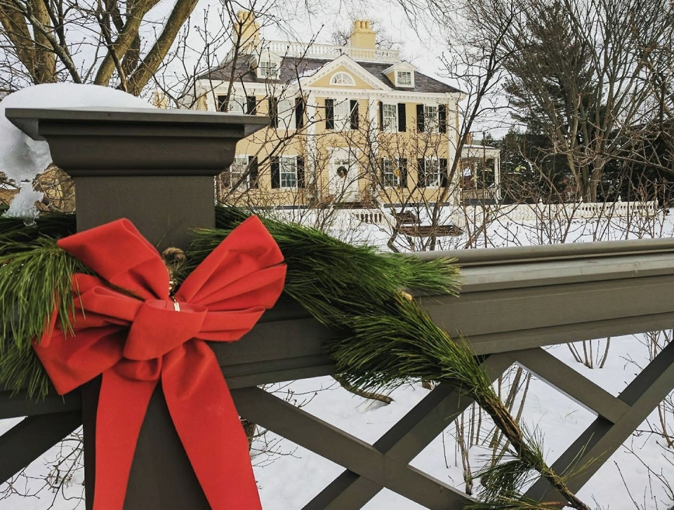 Red Christmas bow on a fence post in front of a snowy yellow mansion at Longfellow House
