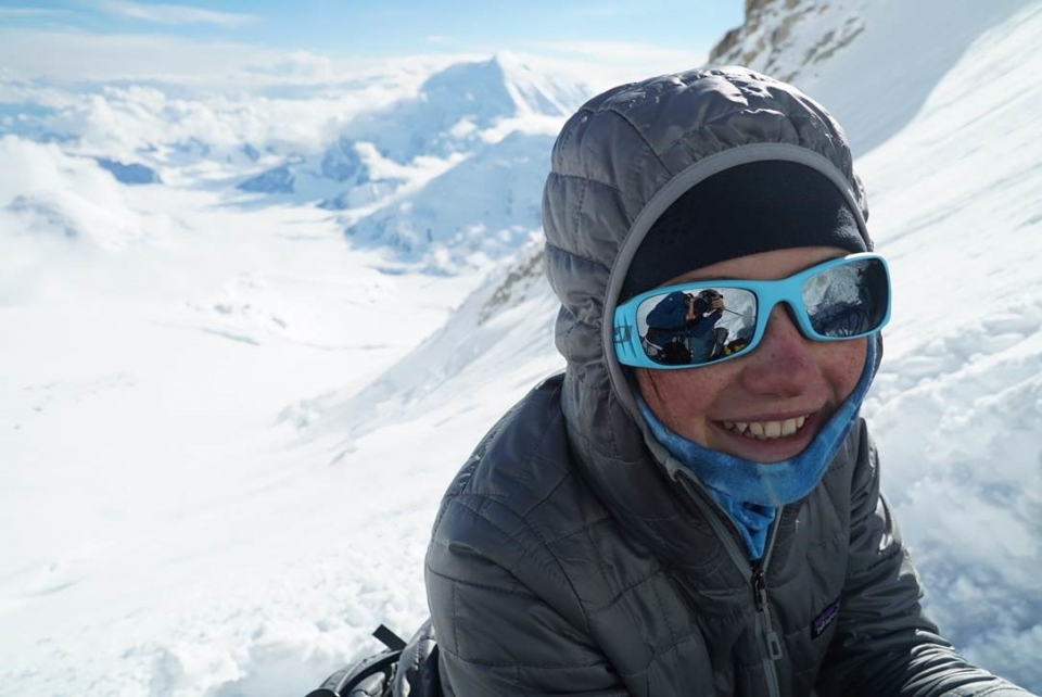 Close up of Lucy bundled up in winter coat and wearing sunglasses, smiling, snow covers the mountain in the background