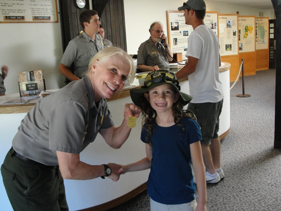 Lucy shakes hands with a National Park Service Ranger as she receives her Junior Ranger badge from Wind Cave National Park, standing inside the visitor center