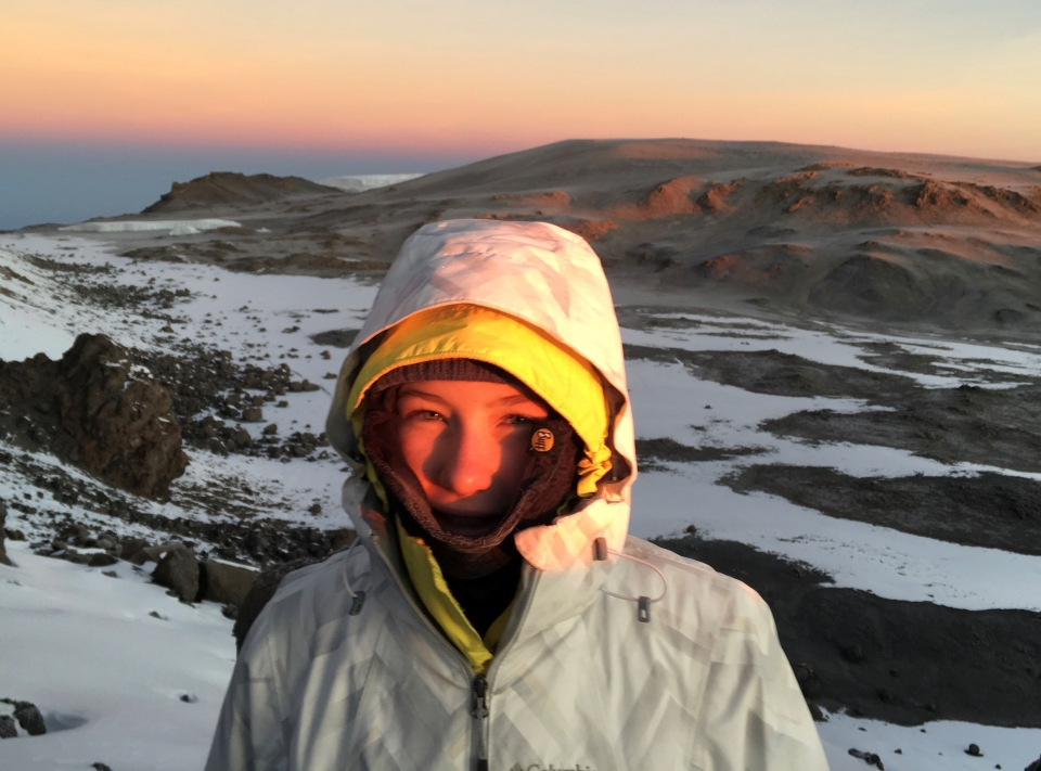 Lucy bundled up in winter coat standing on top of mountain, snow on the ground, and blue orange red sky in background