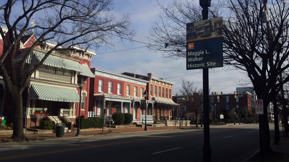 A blue sign with the historic red building of Maggie L Walker National Historic Site in the background