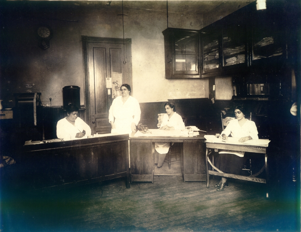 Black and white photo of Maggie Walker and 3 other women at the St. Luke Herald newspaper office