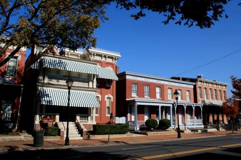 A street-side view of the brick red Maggie L. Walker National Historic Site and the neighboring buildings.