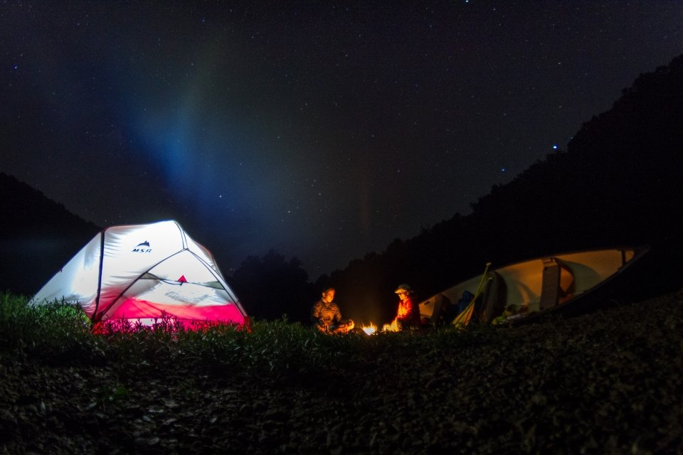 Two poeple camping out with a canoe under a night sky at Mammoth Cave National Monument