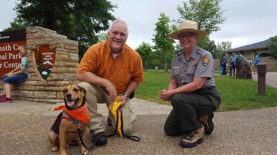 A dog sitting with his owner and a park ranger outside the Mammoth Cave National Park Visitor Center