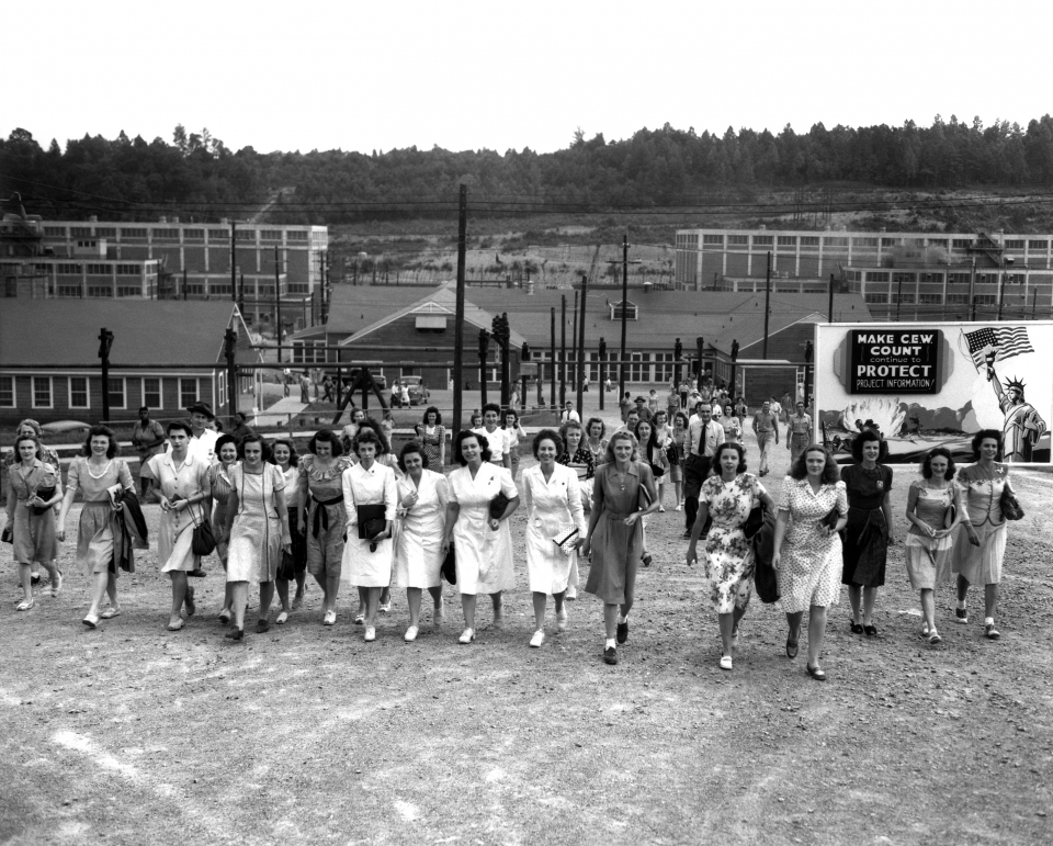 Black and white image of a group of women walking away form a building at the Y-12 Plant in Oak Ridge, TN