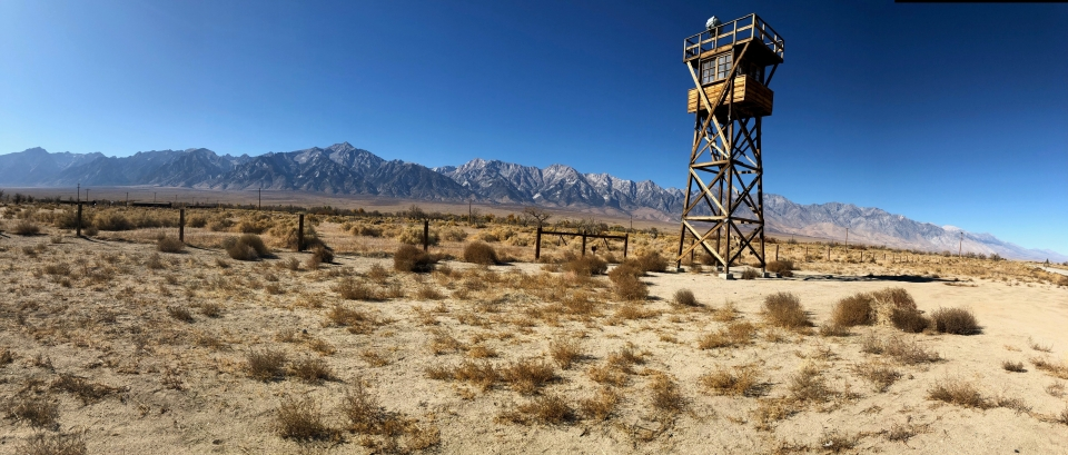 A wooden guard tower looms over a desolate, sandy landscape. A mountain range hangs in the background