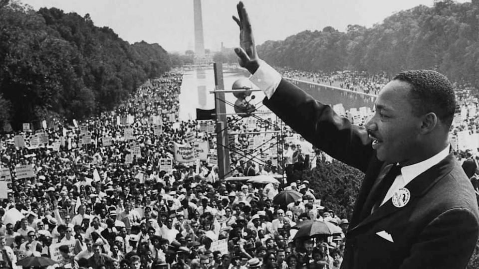 Dr. Martin Luther King, Jr. waves at a crowd gathered for the March on Washington in 1963 on the National Mall