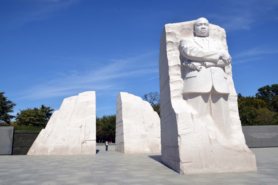 The Martin Luther King Jr. Memorial towers against a bright blue sky at National Mall and Memorial Parks.
