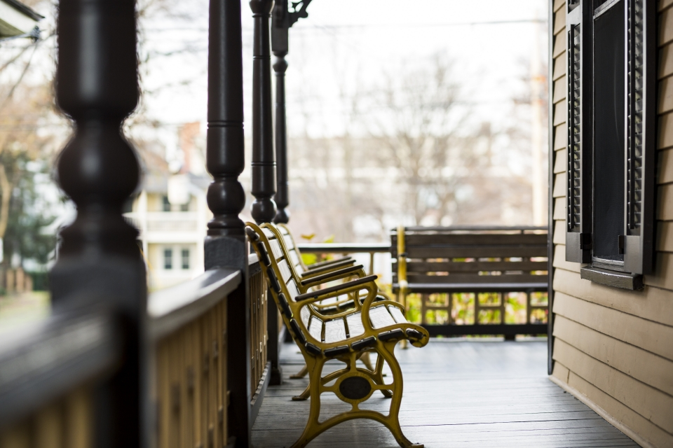 A painted porch in a warm light. Two wooden and metal benches sit on the porch