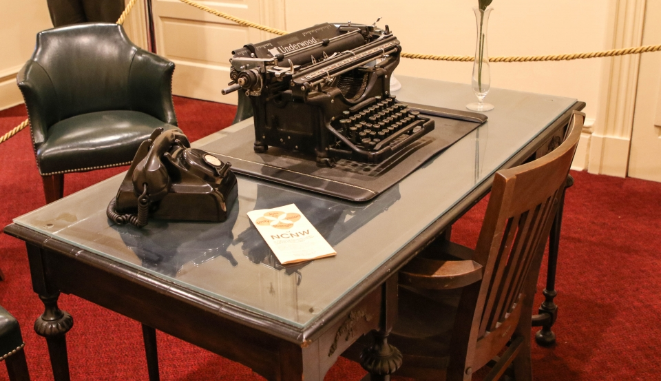 Desk with a telephone, typewriter, and pamphlet on top