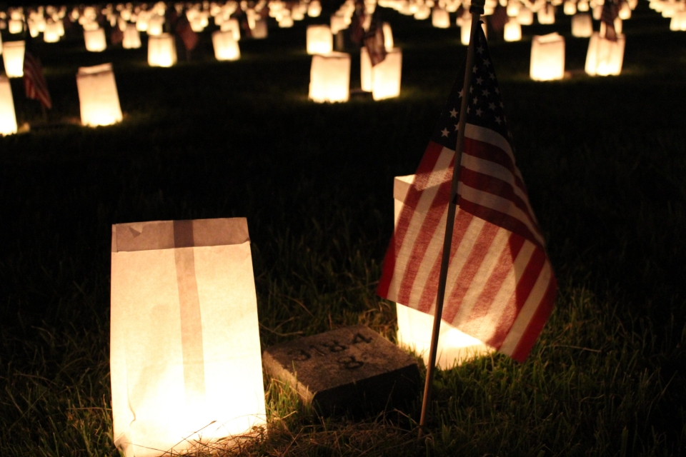 Small American flag next to two candle-lit paper bag luminaries at night