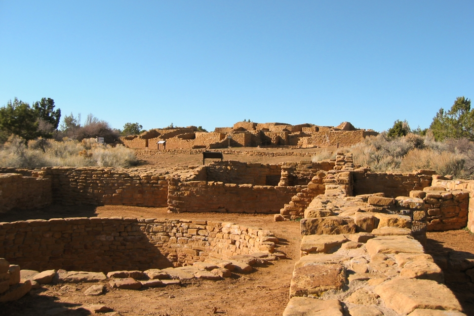 View across low, stone-masonry walls, both square and round. In the background is a one- and two-story remains of a multi-roomed pueblo.
