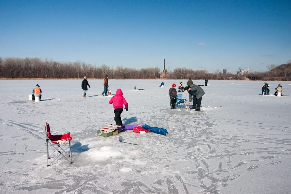 Small groups of people ice fishing on a frozen Pickerel Lake at Mississippi National River and Recreation Area