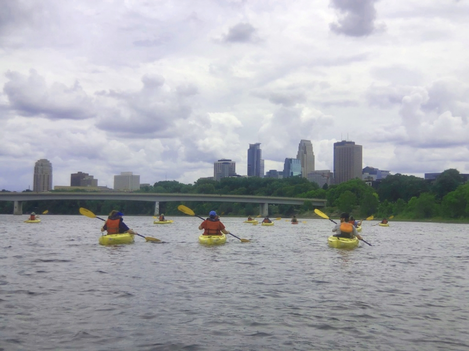 A group of teachers in single kayaks, wearing orange lifejackets, paddle along the Mississippi River