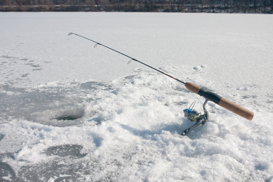 ice fishing hole, with fresh ice shavings lining the hole in the ice, with a fishing rod resting on the solid ice.