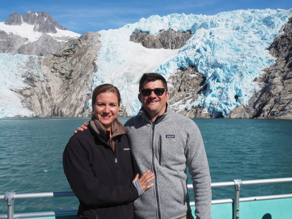 Mo Gallo and her husband stand on the deck of a boat, with a glacier in the background