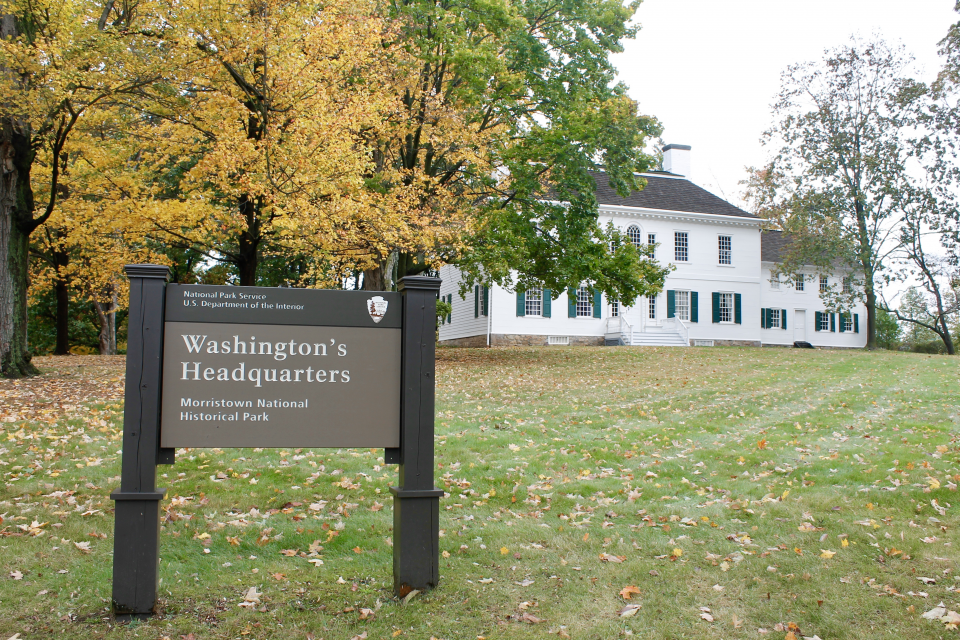 """A """"Washington's Headquarters"""" sign stands before a three-story, white Georgian style home in Morristown, NJ."""