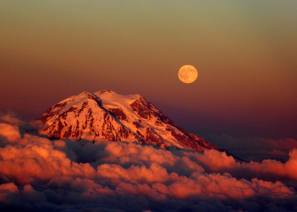 A setting sun casts a red hue over the clouds surrounding Mount Rainier with a yellow-orange moon above.