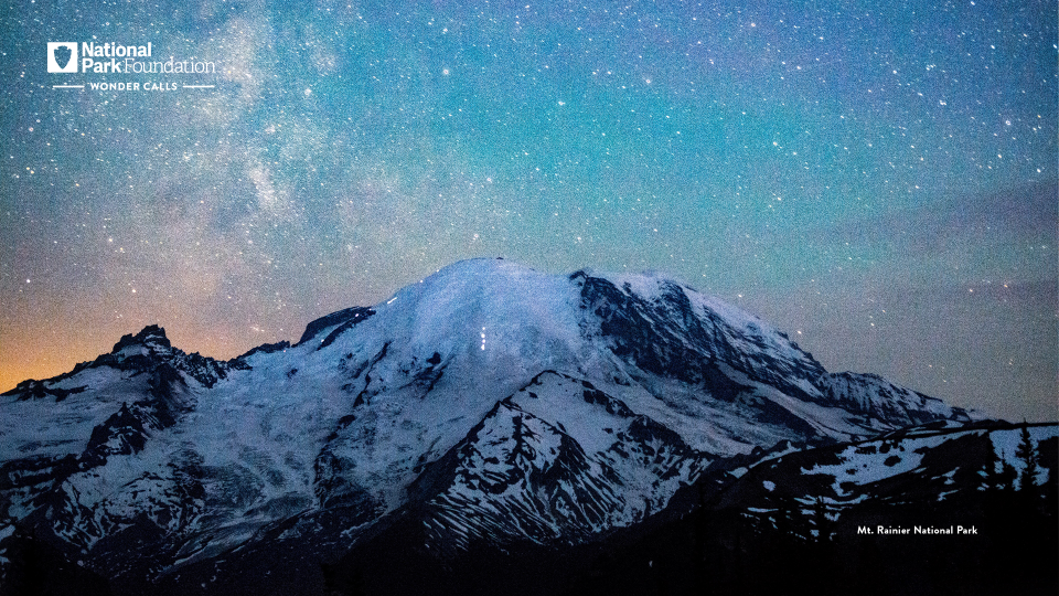 The starry night sky is seen in technicolor over a snowy mountain peak