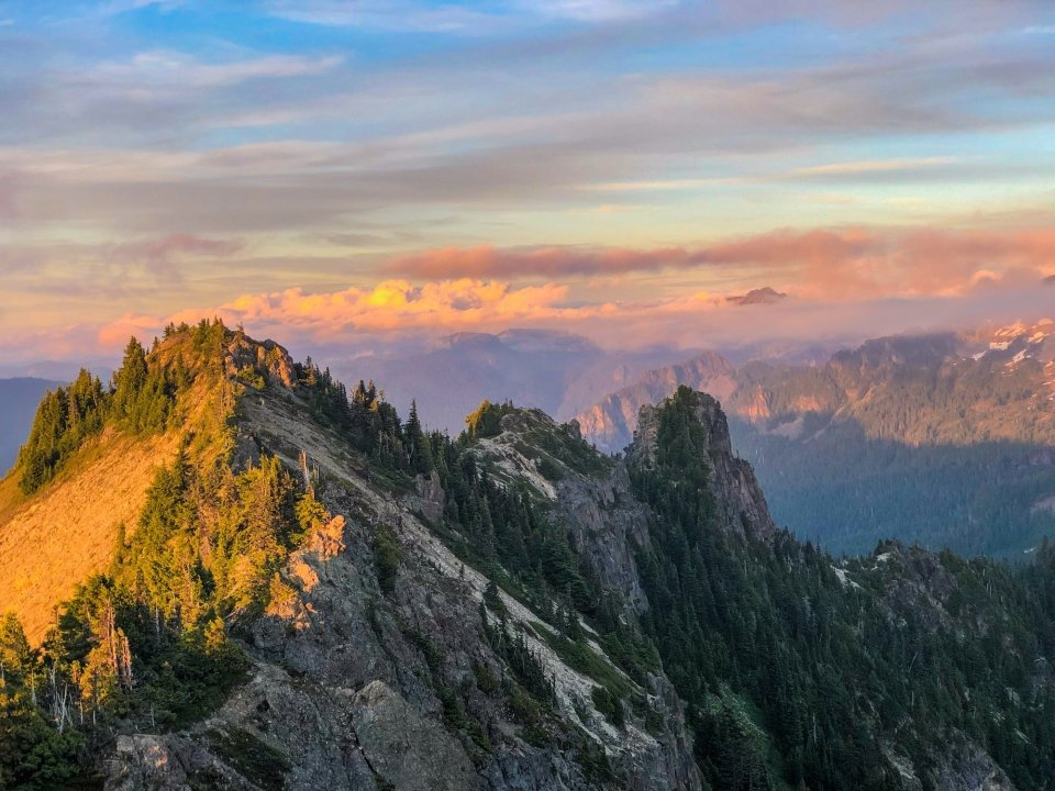A view of peak turning golden in the sunset with a cloudy sky in the background.