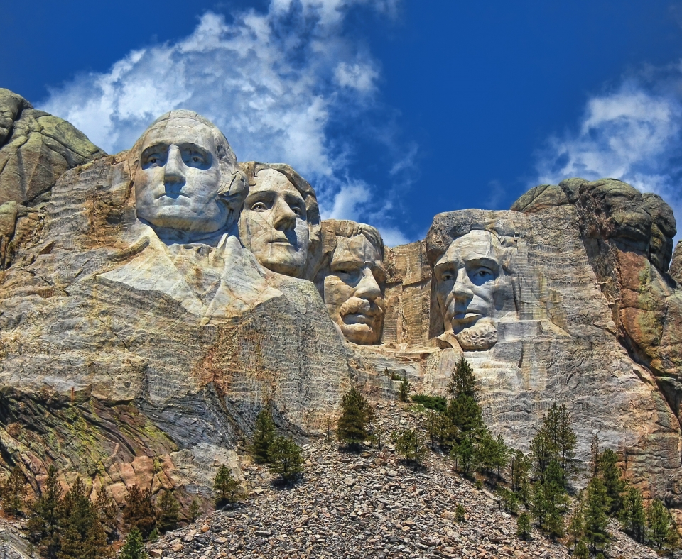Under a bright blue sky with thin white clouds, the iconic figures carved into Mount Rushmore appear even grander compared to the green trees that stand below the monument.