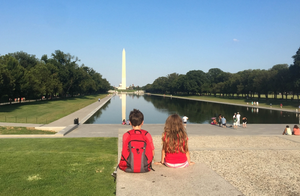 Two kids looking across the Reflecting Pool at the Washington Monument, National Mall & Memorial Parks