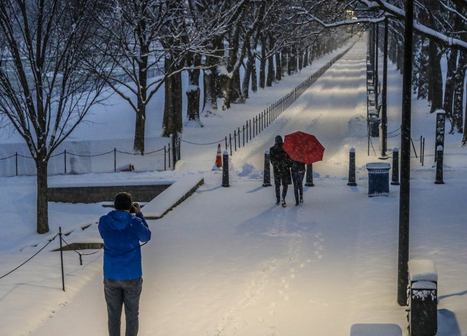 Man taking a picture of a couple with a red umbrella walking on a snow-covered trail