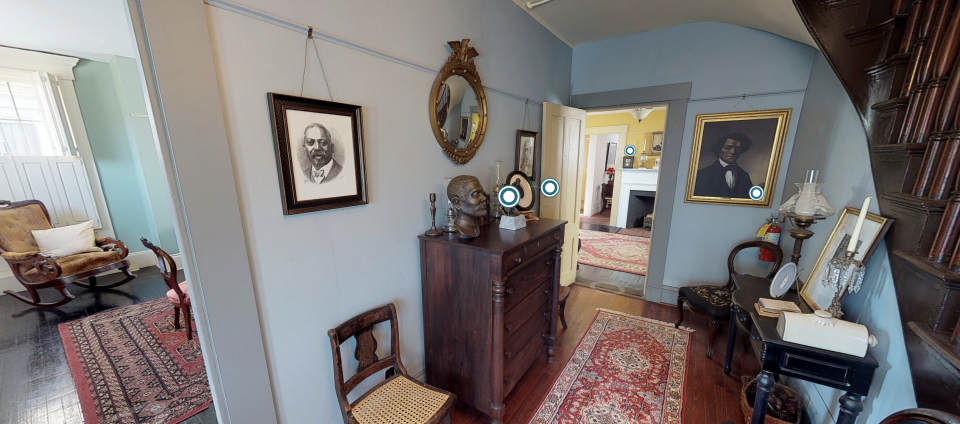 Screenshot of a virtual tour through a historic house. An entryway in the house - blue walls, a picture of Frederick Douglass hangs on the wall.