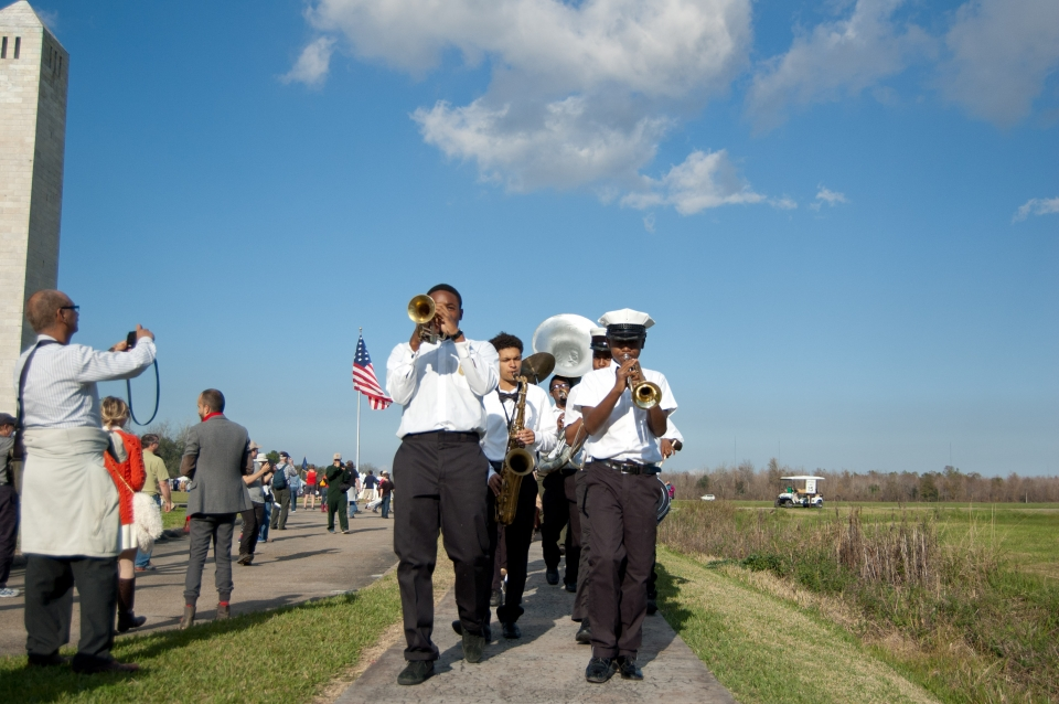 The brass second line marching outside under blue skies at New Orleans Jazz National Historical Park