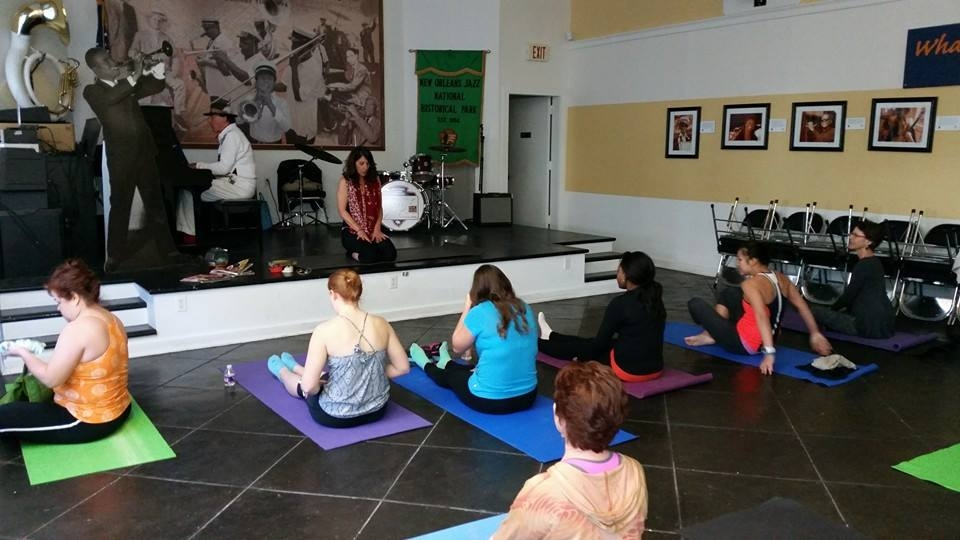 A group of people sitting on yoga mats in front of a man playing the piano at New Orleans Jazz National Historical Park
