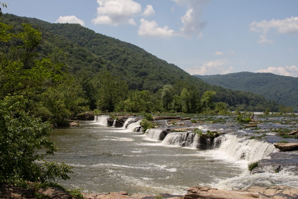 The water falling over the short Sandstone Falls surrounded by greenery at the New River Gorge National River