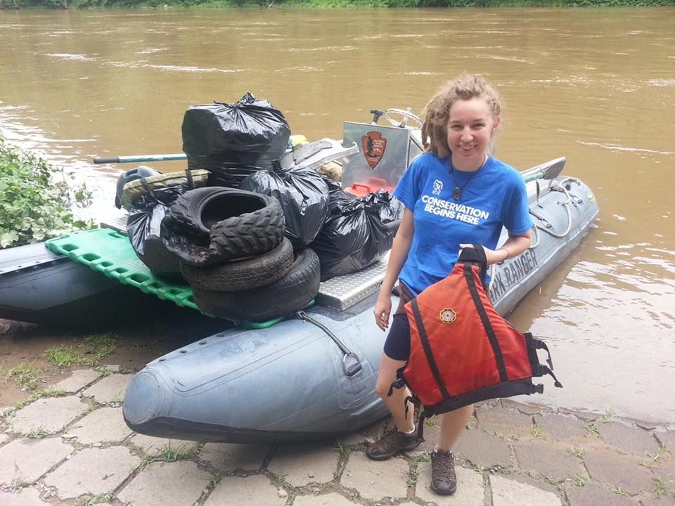 """A woman wearing a """"Conservation Begins Here"""" t-shirt standing next to a Park Ranger boat at the New River Gorge National River"""