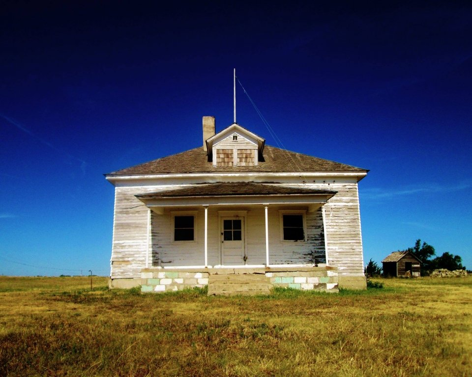 The District No. 1 schoolhouse at Nicodemus National Historic Site stand alone in a field against a backdrop of a clear blue sky.