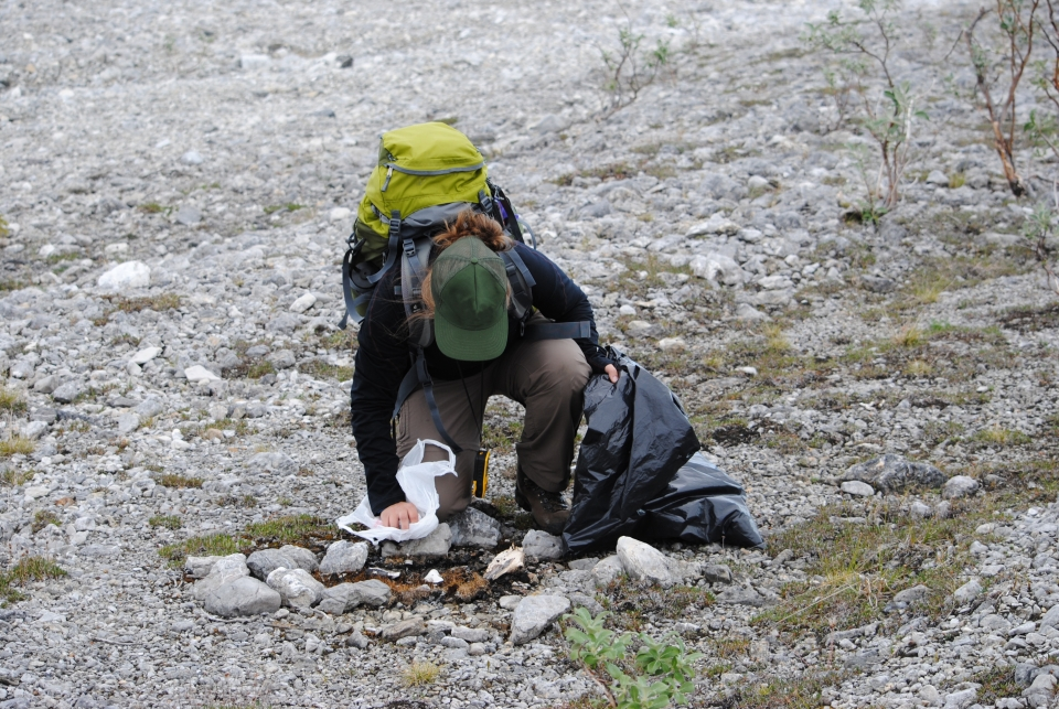 woman removes garbage from under a rock