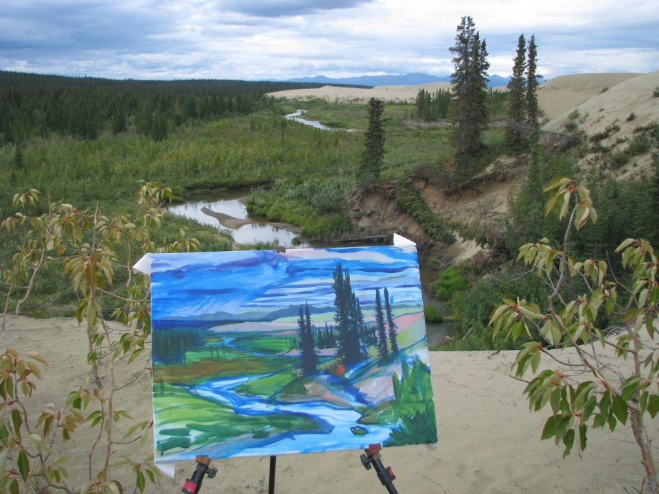 Artwork - a painting of a river and spruce trees - in front of the scenery that inspired it