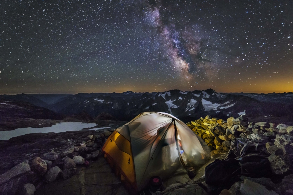 A camper sits within an illuminated tent with the Milky Way overhead at North Cascades National Park.