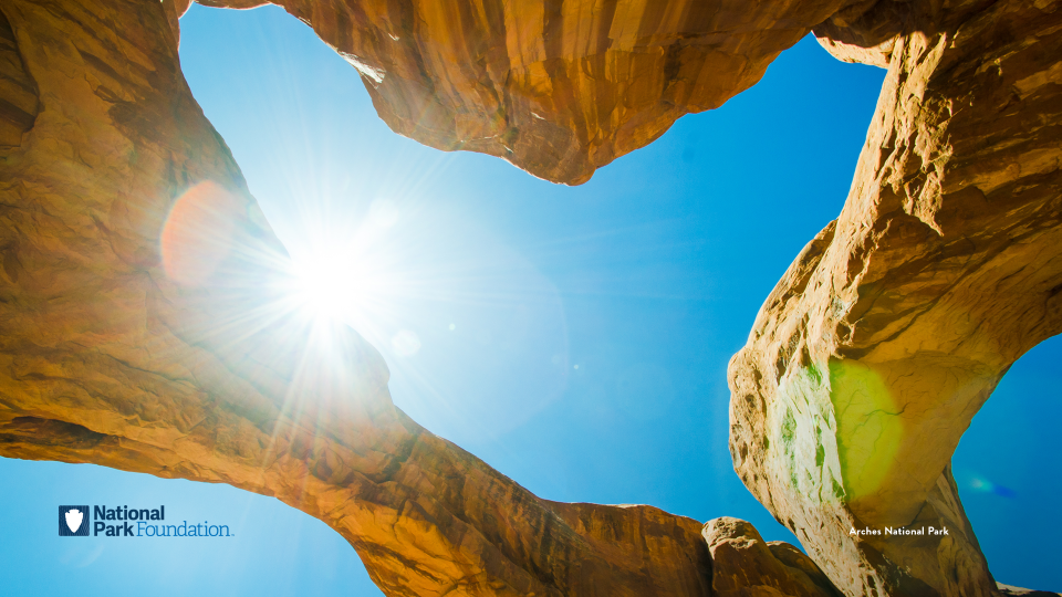 Looking up at a heart-shaped sky through sandstone arches at Arches National Park
