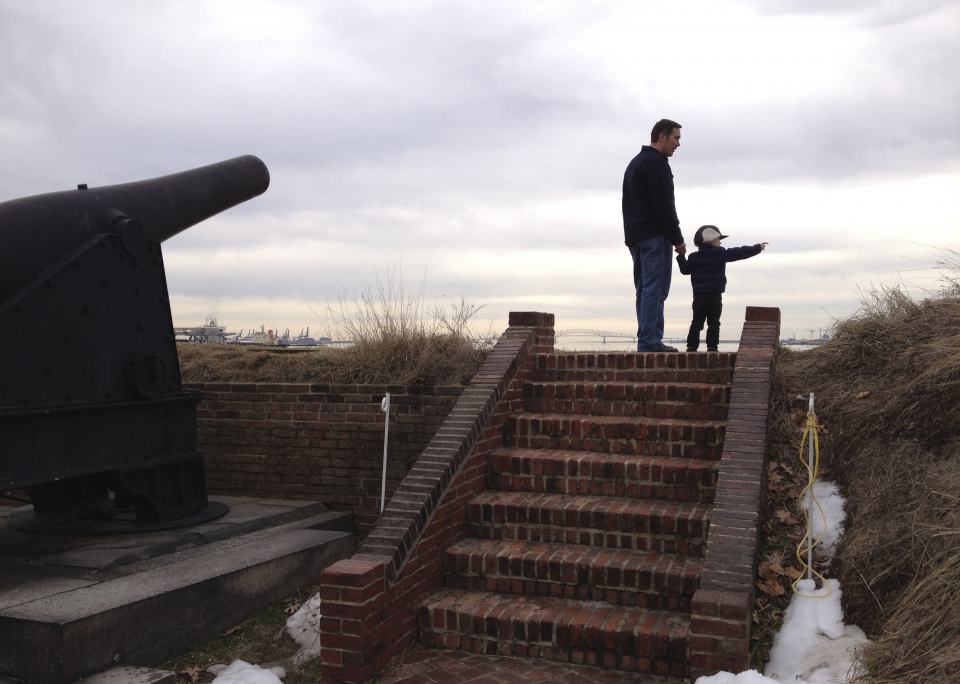 NPF staffer Marjorie's husband looks out over the harbor at Fort McHenry National Monument and Historic Shrine with their son.