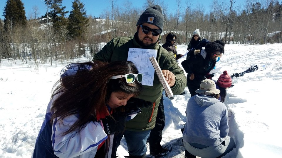 A group of students in the snow at Grand Teton National Park learning orientieering